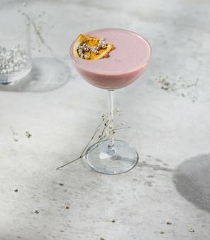 Vista lateral do coquetel de frutas rosa decorado com fatia de laranja seca em um copo na parede branca