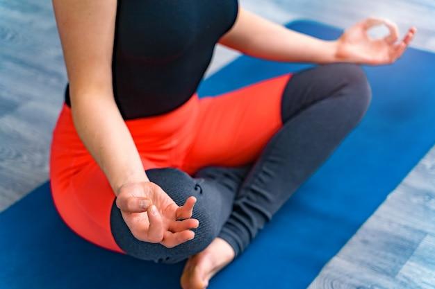 Vista lateral do corpo da mulher fazendo yoga sentado esteira azul dentro de casa. mulher exercitando vital e meditação para o clube de estilo de vida fitness. fechar-se. saudável e yoga