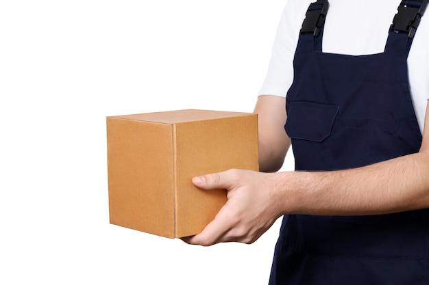Vista lateral do corpo do homem de macacão azul escuro e uma t-shirt branca dando caixa de papelão, isolada no fundo branco. conceito de entrega.