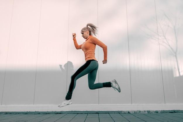 Vista lateral do corredor feminino no sportswear correndo rápido na rua
