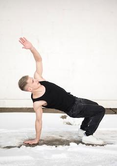 Vista lateral do dançarino de hip hop posando fora