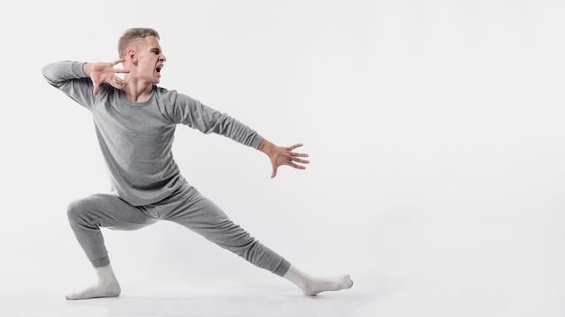 Vista lateral do dançarino masculino em agasalho e meias posando