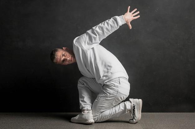 Vista lateral do dançarino masculino posando com fumaça