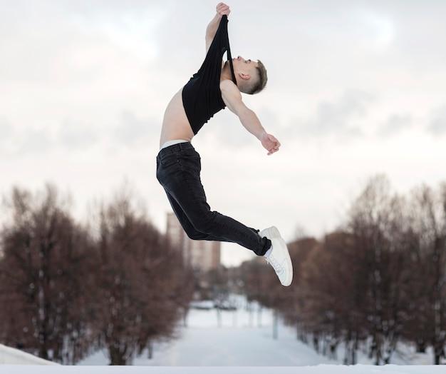 Vista lateral do dançarino masculino posando enquanto no ar