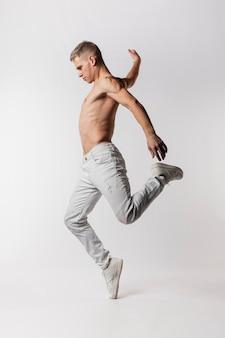 Vista lateral do dançarino sem camisa em jeans e tênis dançando
