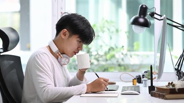 Vista lateral do designer criativo masculino com fone de ouvido usando o tablet digital e a caneta stylus enquanto bebe café no escritório moderno.