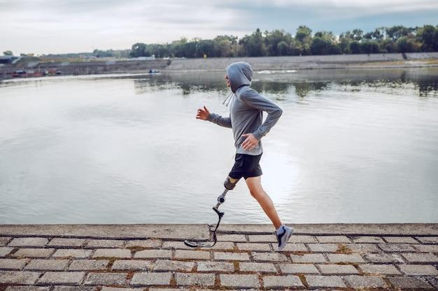 Vista lateral do desportista deficiente caucasiano saudável em roupas esportivas e com perna artificial correndo no cais.