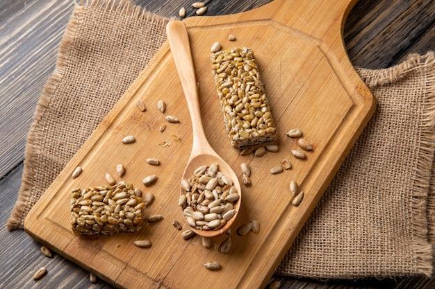 Vista lateral do doce kozinaki de sementes de girassol com uma colher de pau na tábua de madeira