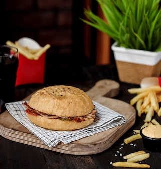 Vista lateral do doner de kebab com carne e legumes no pão na tábua de madeira
