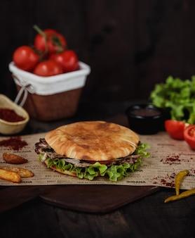 Vista lateral do doner kebab com batatas fritas em uma tábua de madeira