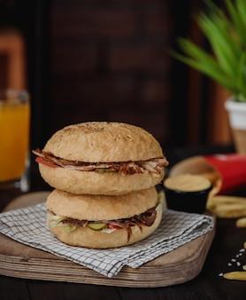 Vista lateral do doner kebab no pão pita em cima um do outro em uma placa de madeira