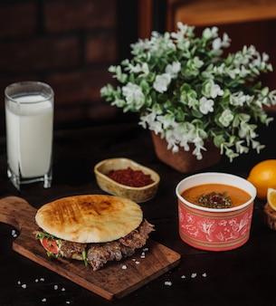 Vista lateral do doner kebab no pão pita em uma placa de madeira servida com sopa de lintel e ayran bebida na mesa preta