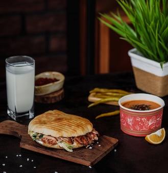 Vista lateral do doner kebab no pão pita em uma placa de madeira, servida com sopa de verga ayran bebida e em conserva pimentas verdes quentes na parede de madeira