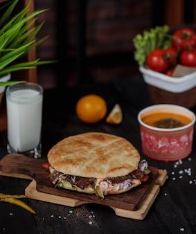Vista lateral do doner kebab no pão pita em uma placa de madeira, servida com sopa de verga e ayran bebida na mesa