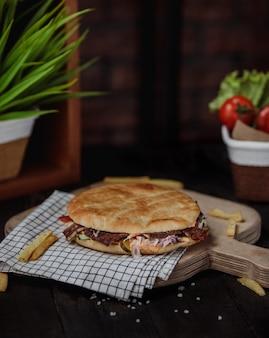 Vista lateral do doner kebab no pão pita em uma placa de madeira