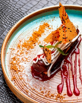 Vista lateral do eclair de chocolate com chantilly e morango em um prato decorado com calda de baga e açúcar em pó