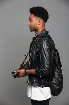 Vista lateral do elegante homem africano elegante com mochila segurando a câmera fotográfica
