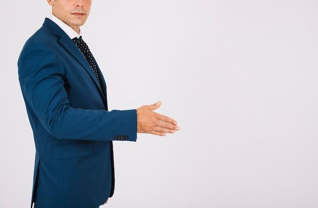 Vista lateral do empresário alcançando a mão