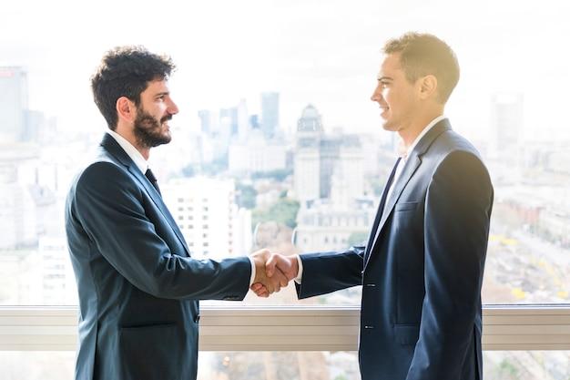 Vista lateral do empresário apertando as mãos uns dos outros