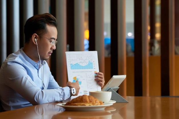 Vista lateral do empresário discutindo métricas de relatório financeiro via videochamada