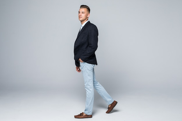 Vista lateral do empresário em jaqueta e jeans se move pelo estúdio isolado no branco