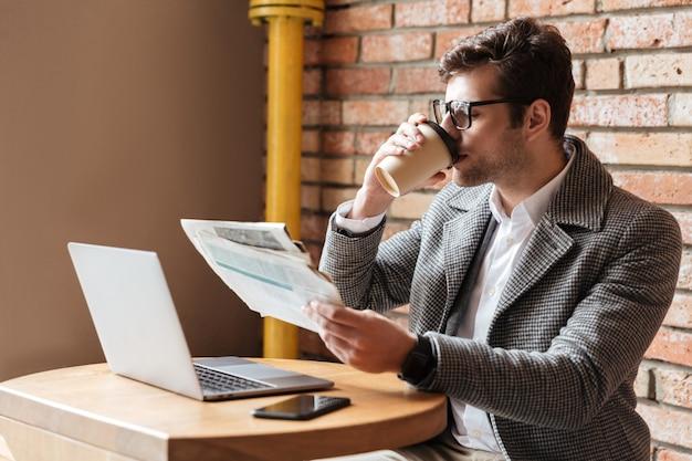 Vista lateral do empresário em óculos, sentado junto à mesa