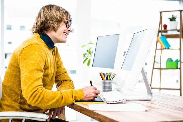 Vista lateral do empresário hipster usando tablet gráfico em seu escritório