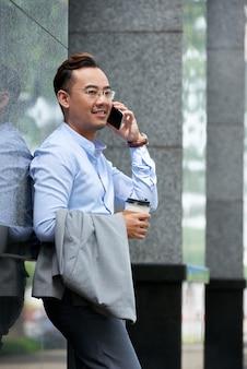 Vista lateral do empresário tendo telefone falar ao ar livre num dia de verão