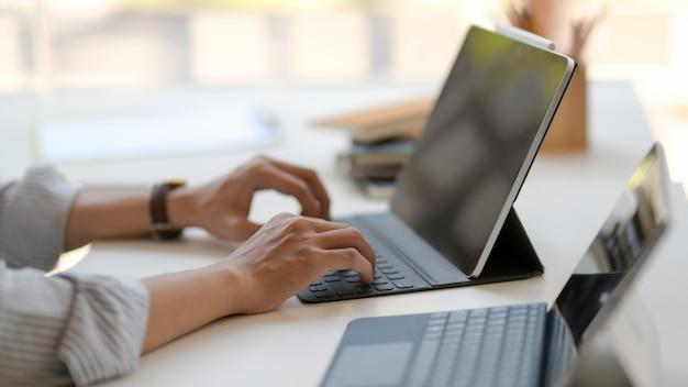 Vista lateral do empresário trabalhando em tablets digitais na mesa branca no local de trabalho moderno