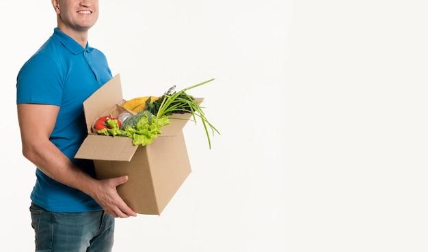 Vista lateral do entregador posando com caixa de supermercado