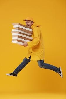 Vista lateral do entregador pulando alto segurando caixas de pizza