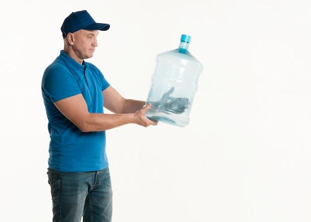 Vista lateral do entregador segurando a garrafa de água