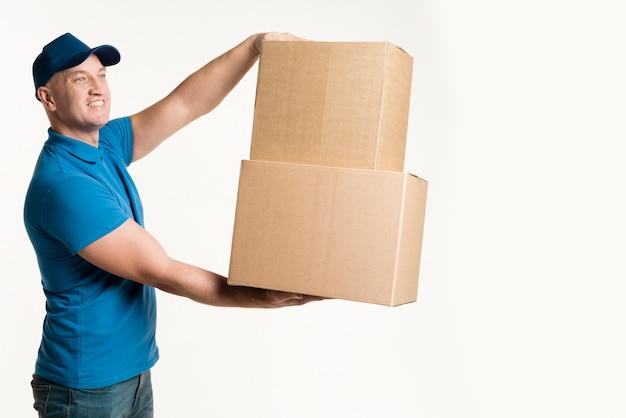 Vista lateral do entregador segurando caixas de papelão nas mãos