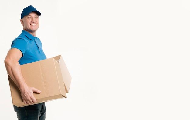 Vista lateral do entregador sorrindo enquanto segura caixas de papelão