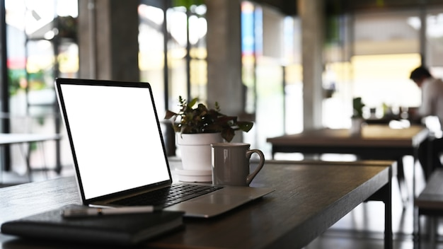Vista lateral do espaço de trabalho moderno com um laptop de computador de tela em branco. tela em branco para montagem de display gráfico.