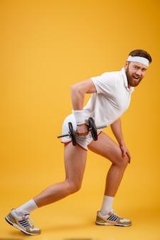 Vista lateral do esportista barbudo fazendo exercício com halteres