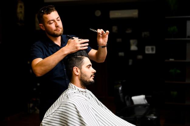 Vista lateral do estilista dando um corte de cabelo