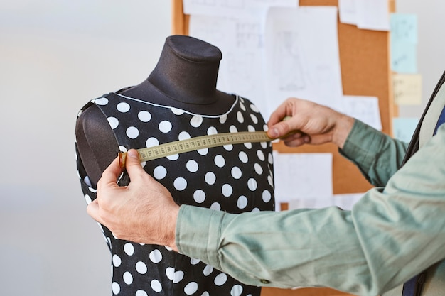 Vista lateral do estilista masculino medindo a forma do vestido no ateliê