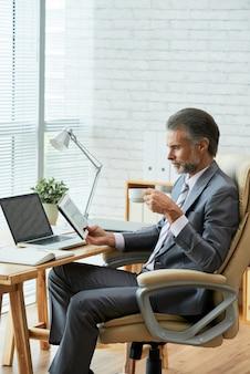 Vista lateral do executivo de negócios sênior, olhando para o tablet digital touchscreen enquanto bebe café