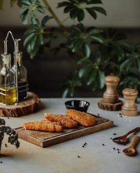 Vista lateral do filé de frango frito na farinha de rosca em uma placa de madeira