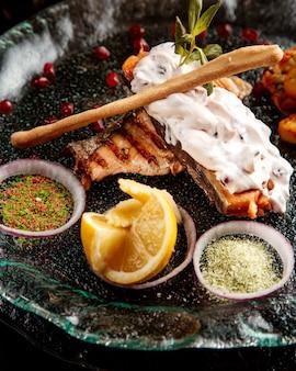 Vista lateral do filé de peixe assado, guarnecido com legumes especiarias e molho em um prato