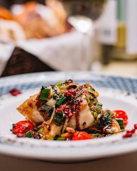 Vista lateral do filé de peixe grelhado com legumes, servido com ervas frescas e molho em um prato