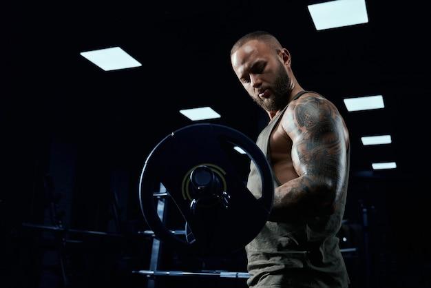 Vista lateral do fisiculturista barbudo treinando bíceps com barra.