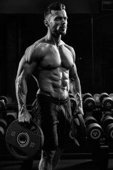 Vista lateral do fisiculturista masculino incógnito tenso sem camisa segurando pesos nos braços.