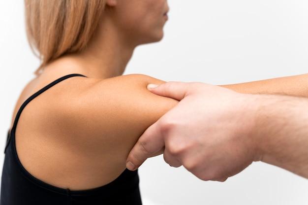 Vista lateral do fisioterapeuta massageando o braço da mulher