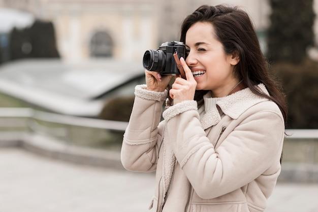 Vista lateral do fotógrafo feminino ao ar livre
