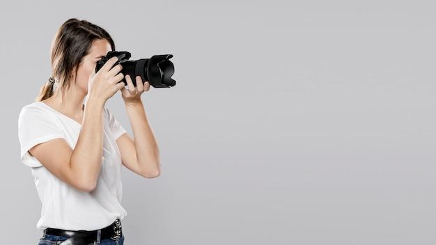 Vista lateral do fotógrafo feminino com espaço de cópia