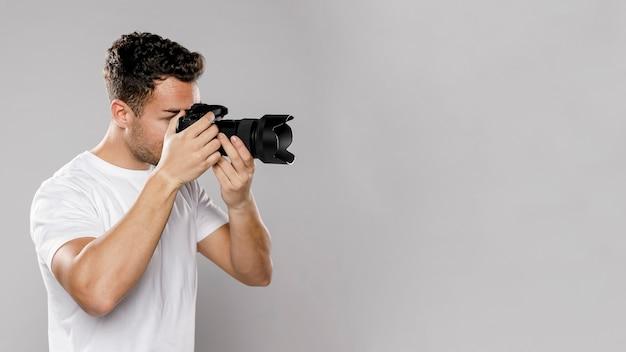 Vista lateral do fotógrafo masculino com espaço de cópia