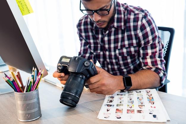 Vista lateral do fotógrafo trabalhando na mesa