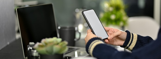Vista lateral do freelancer feminino olhando no smartphone no local de trabalho moderno escuro